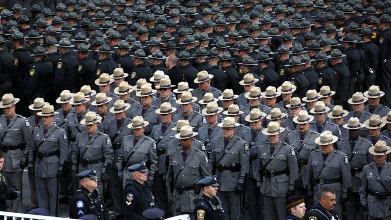 Pennsylvania State Police troopers line up outside of the Blair County Convention Center in Altoona, Pa.