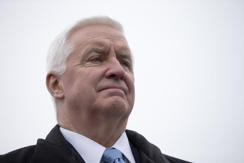 Outgoing Gov. Tom Corbett stands before Tom Wolf as he takes the oath of office to become the state's 47th governor on Tuesday, Jan. 20, 2015.