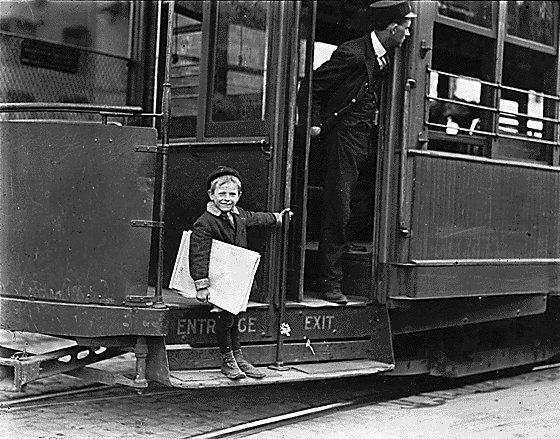 "A ""trolley  newsboy"" holds on to the entrance of a streetcar as the operator looks out."