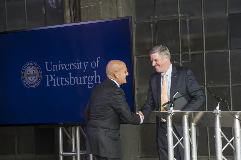 University of Pittsburgh Chancellor Patrick Gallagher shakes hands with UPMC CEO Jeffrey Romoff at the announcement of the new UPMC Immune Transplant and Therapy Center, a joint venture between the university and hospital system.
