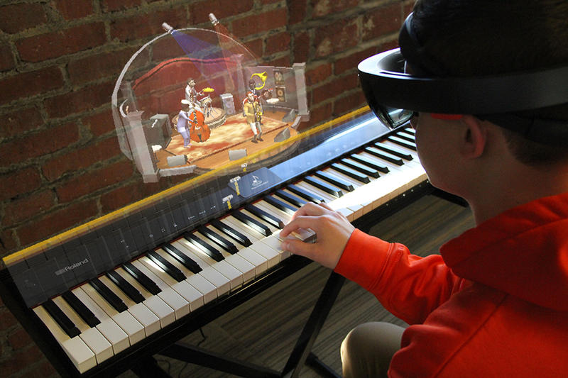 A Music Everywhere user mid-gameplay. The animations shown hovering over the piano are what the user is seeing through the Microsoft HoloLens augmented reality headset.