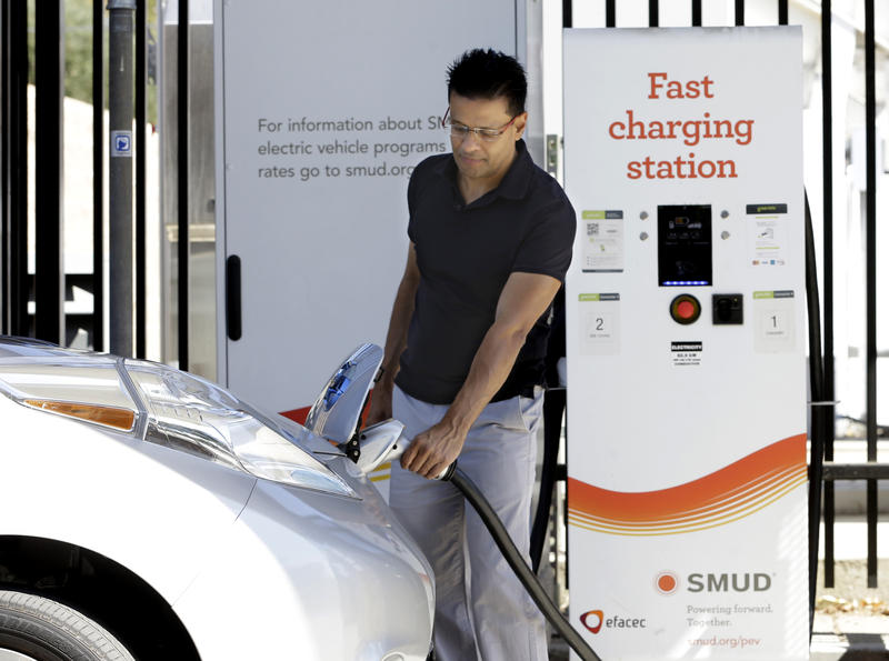 A man unplugs a charger from his electric vehicle at the Sacramento Municipal Utility District charging station in Sacramento, Calif. on Thursday, Sept. 17, 2015.