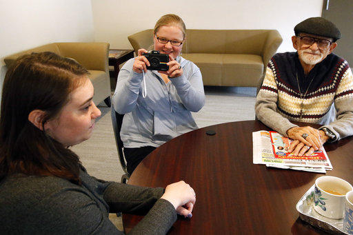 Masha Gregory, center, takes a polaroid photo of fellow resident Elise Mote, at an apartment complex in Heidelberg, Pa., designed for adults with autism. A new study from Pitt looked at ways to improve communication skills for adults with autism.