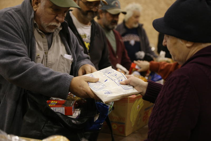 Food bank recipients are given items, such as dried mashed potatoes, canned vegetables and instant noodles.