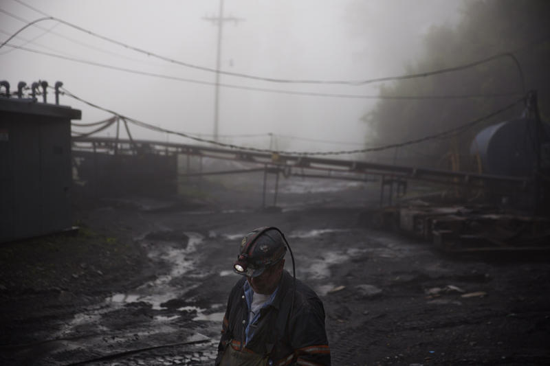 "Coal miner Scott Tiller walks through the morning fog before going underground in a mine less than 40-inches high in Welch, W.Va. In December, the Trump administration announced plans to make ""less burdensome"" a regulation to shield miners from coal dust."