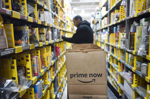In this Dec. 20, 2017, file photo, a clerk reaches to a shelf to pick an item for a customer order at the Amazon Prime warehouse in New York.