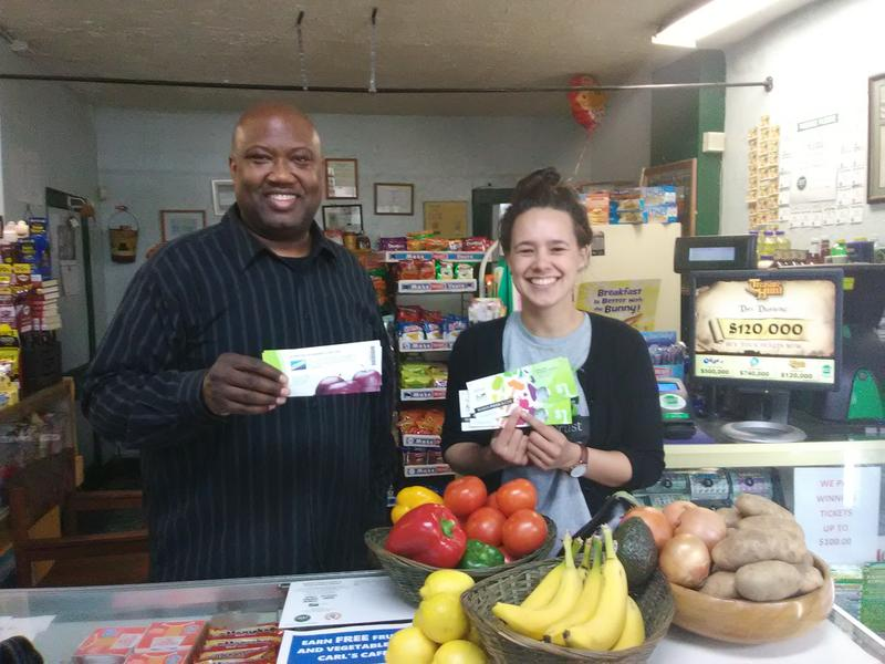 Carl Lewis, owner of Carl's Cafe, and Emily Schmidlapp of the nonprofit The Food Trust, hold Food Bucks which can be used to purchases fresh fruits and vegetables.