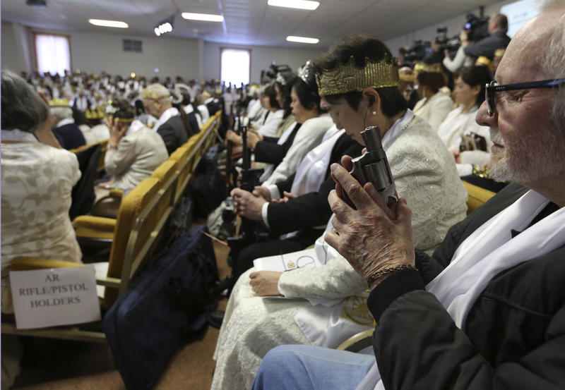 A man holds an unloaded weapon during services at the World Peace and Unification Sanctuary, Wednesday, Feb. 28, 2018 in Newfoundland, Pa.