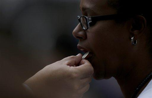 A woman receives communion during a Mass celebrated by Pope Francis Sunday, Sept. 27, 2015, in Philadelphia. The Greensburg Diocese has detailed guidelines on how to participate in Mass, but avoid becoming prone to the flu.