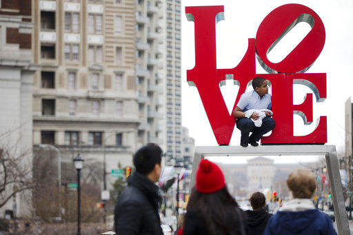 "A teen poses in front of the ""LOVE"" statue in Philadelphia's John F. Kennedy Plaza, also known as Love Park, on March 27, 2015."