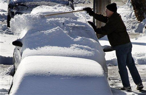 A resident of Greenfield brushes snow off a car.