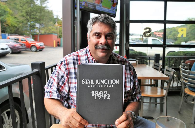 A.J. Boni, Perry Township Supervisor, poses with a copy of the Star Junction centennial memory book at a Primanti Bros. in Plesant Hill, Pa., on Tuesday, Sept. 12, 2017.