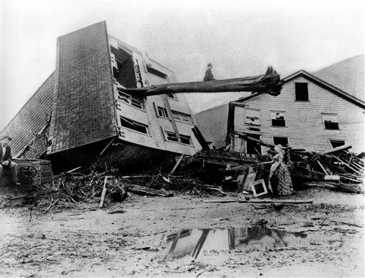 In this historical photo from May 31, 1889, survivors stand by homes destroyed by the Johnstown flood.