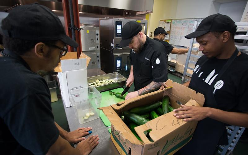 Chef trainer Travis Torsell, 38, of the South Side, shows students James Dreher (left), 25, and Recardo Williams, 29, how to properly cut zucchini at the Community Kitchen Pittsburgh in Hazelwood.