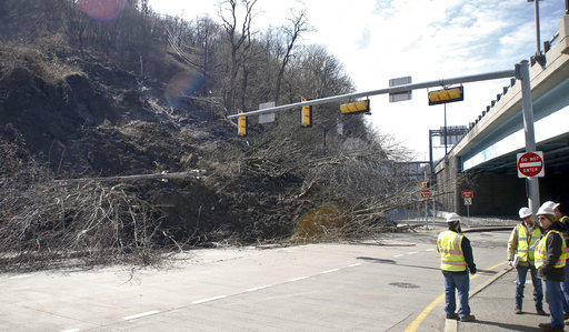 Workers stand along a roadway shut down in February after a landslide. Clearing work was still continuing in various parts of the city when a storm prompted another slide ripped 300 feet of highway on Route 30 in East Pittsburgh Saturday, April 7, 2018.