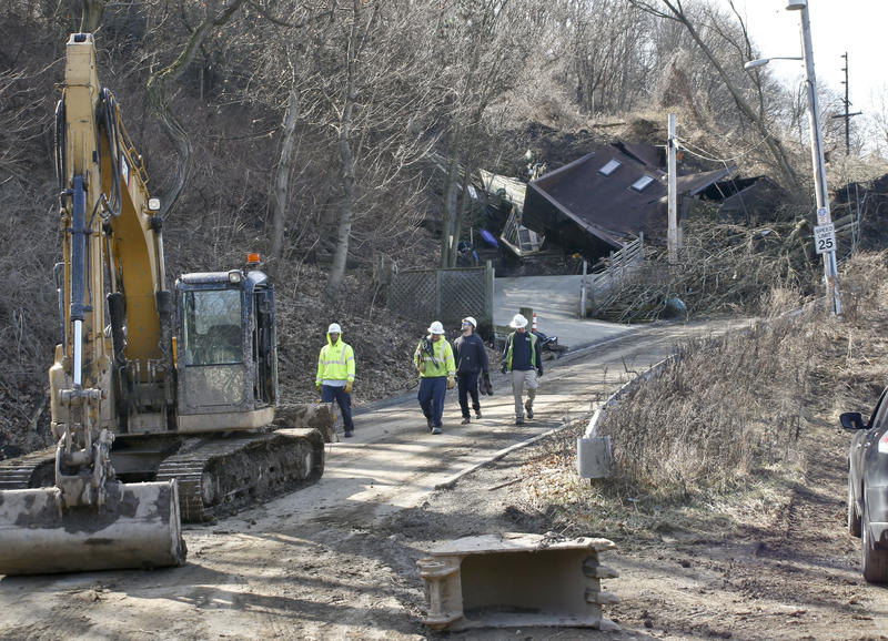 Clearing work continues Monday, Feb. 26, 2018, as power company employees walk past a home destroyed by a landslide that started the previous Friday. The landslide in Duquesne Heights poured over a retaining wall and closed a section of roadway.