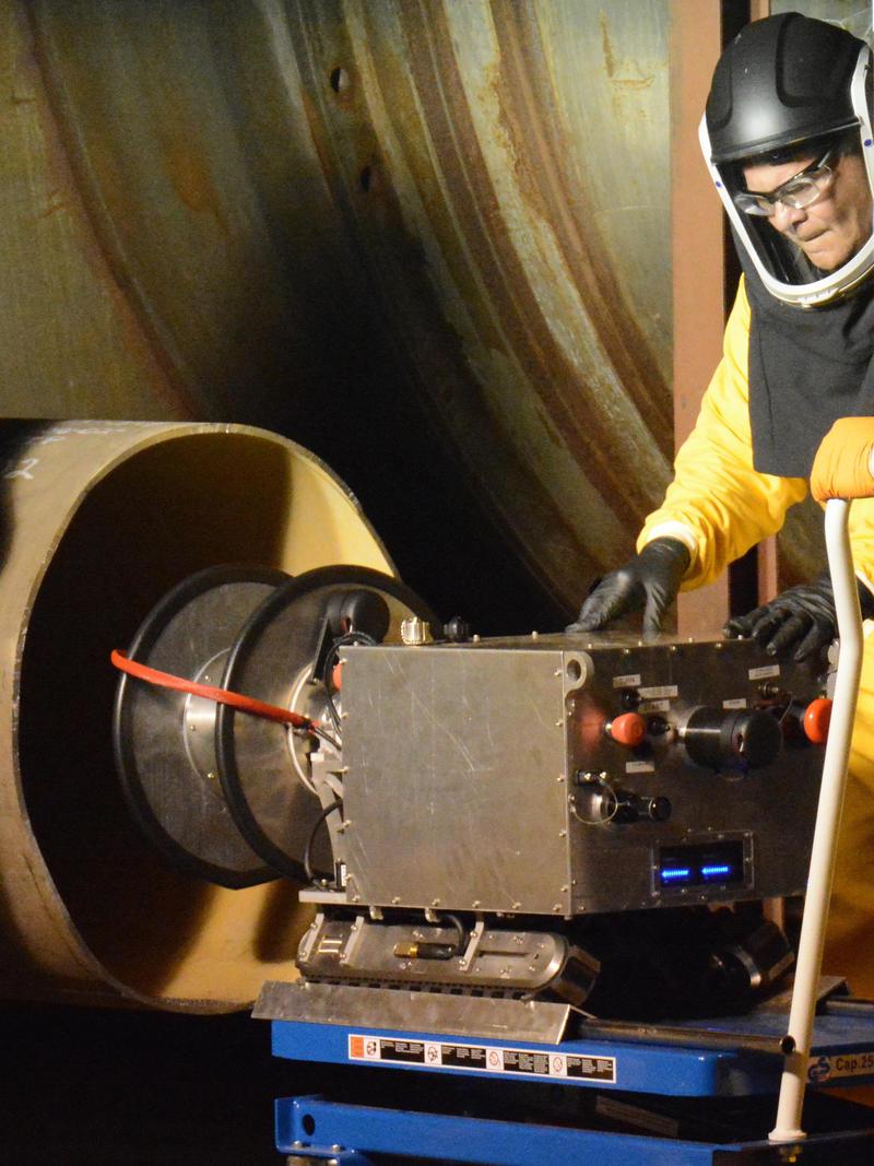 Keith Banks, wearing protective gear, tests RadPiper at the Piketon facility.