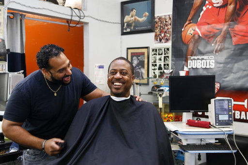 Barber Eric Muhammad, owner of A New You Barbershop, left, jokes with regular customer Marc M. Sims before measuring his blood pressure in Inglewood, Calif., Sunday, March 11, 2018.
