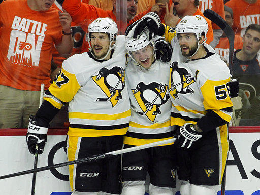 Pittsburgh Penguins' Sidney Crosby, left, and Kris Letang, right, embrace Jake Guentzel after scoring during Game 6 of the first-round NHL Playoff series.