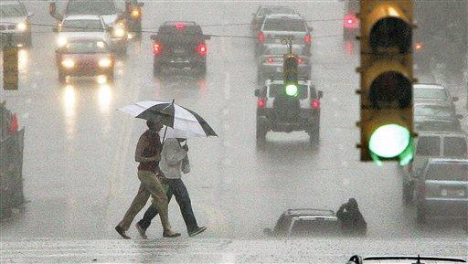 A couple under an umbrella crosses through traffic at an intersection as rain falls along the Boulevard of the Allies.