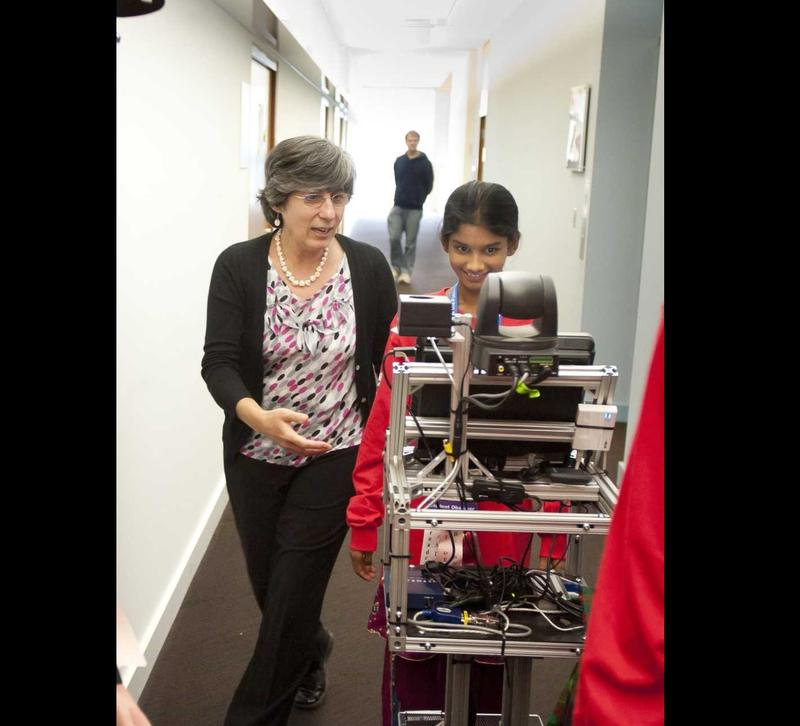 Manuala Veloso and a student walk with her autonomous robot, CoBot, that runs errands inside the Gates and Hillman centers.