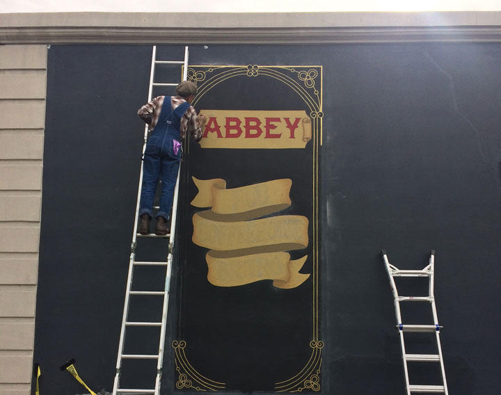 Shaknaitis paints a sign for The Abbey on Butler Street.