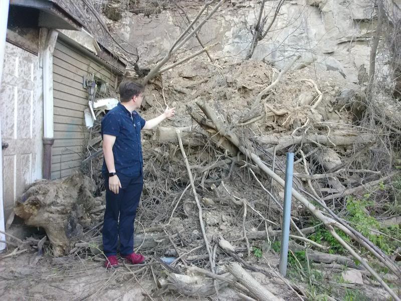 Spring Hill resident Randal Miller, 36, gestures to the landside that damaged his home.