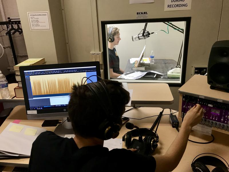 Barack Obama Academy of International Studies sophomore Sam Bisno monitors the audio levels of Piper Walsh, recording audio for children's books at the Carnegie Library for the Blind and Physically Handicapped on Friday May 4, 2018.