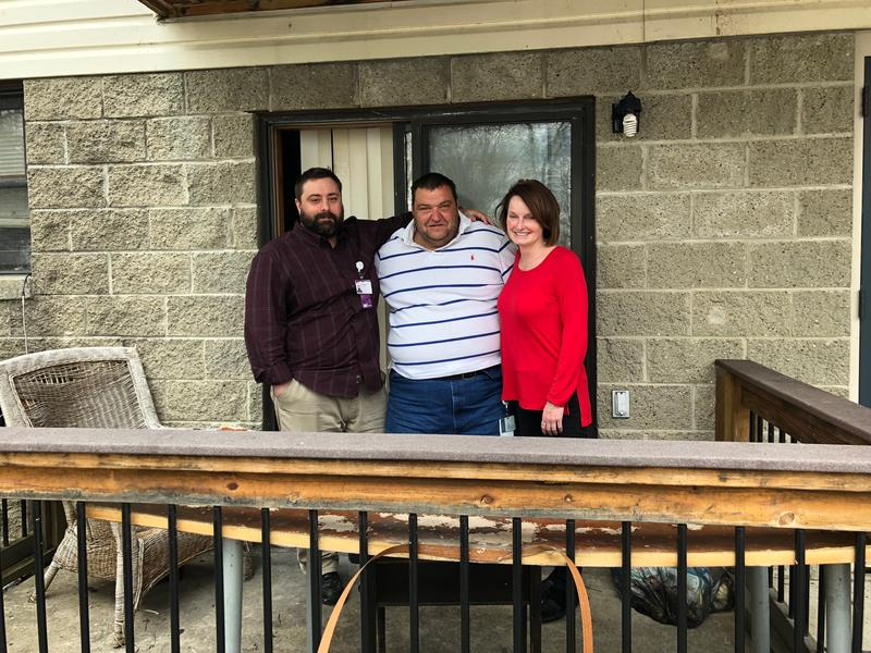 Darren Haggerty, Tom Lefevre and Whitney Amoroso on the back porch of Lefevre's apartment. Lefevre is a patient in UPMC Health Plan's Cultivating Health for Success program. Haggerty, a case manager and Amoroso, a nurse, work for the program.