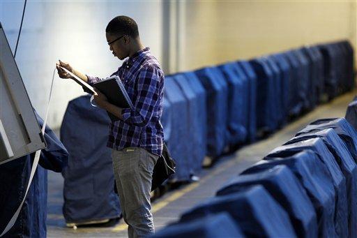 Malcom Kenyatta tests a voting machine Friday, May 6, 2011, in Philadelphia.