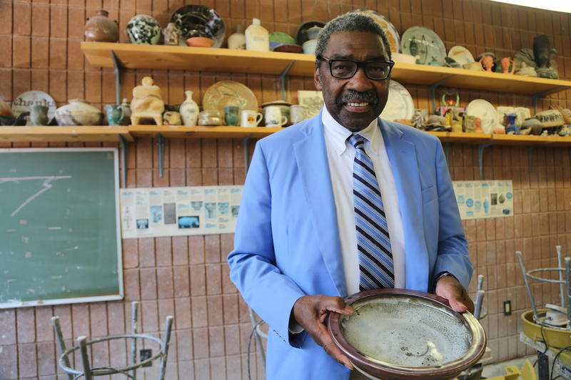 Bill Strickland poses for a portrain in the ceramics studio at the Manchester Bidwell Corporation. He's holding a piece of pottery he made.