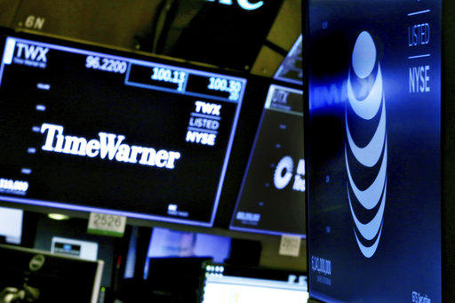 The logos for Time Warner and AT&T appear above alternate trading posts on the floor of the New York Stock Exchange, Wednesday, June 13, 2018. A federal judge has approved the $85 billion mega-merger of the companies.