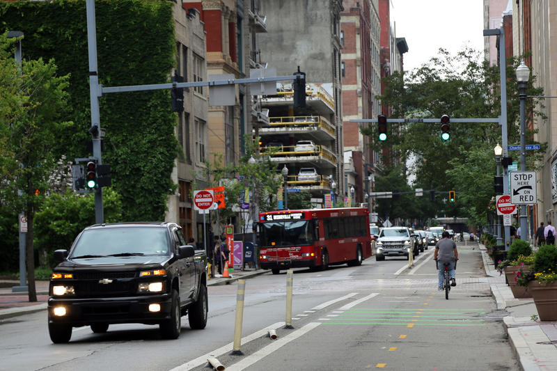 A bicyclist pedals northeast up Penn Avenue in Downtown Pittsburgh on Tuesday, June 5, 2018, as trucks, buses and other vehicles roll by.