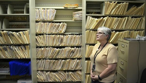 Environmental risk inspector Marilou Yingling stands in front of years' worth of files on lead found in York homes.