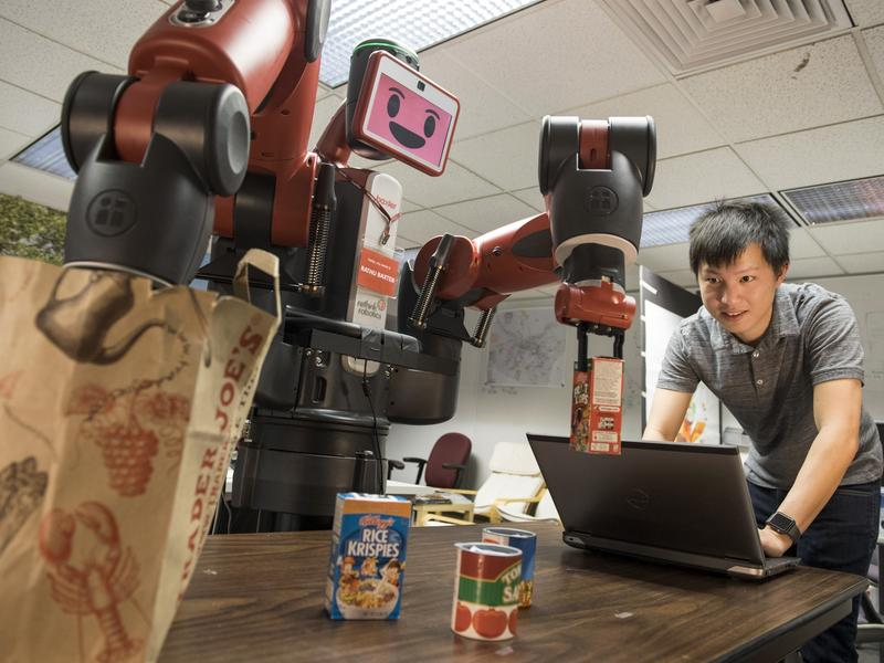 Carnegie Mellon University PhD student Xiang Zhi Tan observes the Baxter robot as it plays a dexterity game.