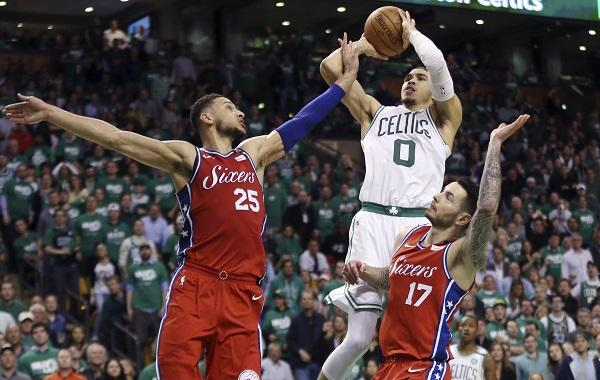 Boston Celtics forward Jayson Tatum (o) shoots against Philadelphia 76ers guard Ben Simmons (25) and guard JJ Redick (17) in the second half of Game 1 of an NBA basketball second-round playoff series, Monday, April 30, 2018, in Boston.