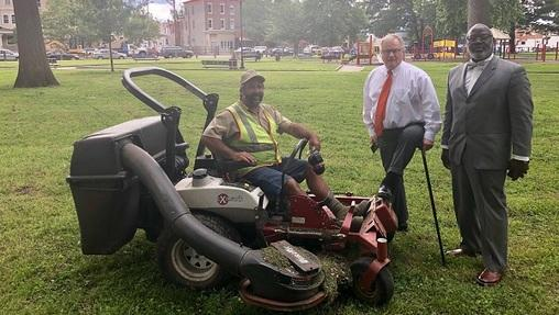 Scott Wagner in Malcom X Park post-cleanup, accompanied by a contractor, supporter and lawnmower.