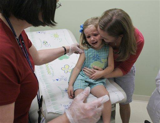 Drennan Barnes, 3, receives comfort from her mother, Jennifer Barnes, after getting a shot of swine flu vaccination at Emory Children's Center on Sept. 2, 2009.