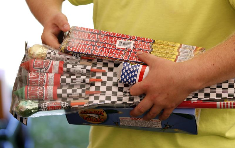 In this Friday, June 16, 2017 photo, Julian Gibson, of Dallas Center, Iowa, holds packages of fireworks before buying them in a tent owned by the Iowa Fireworks Company, in Adel, Iowa.