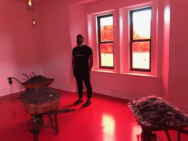 "Ricardo Iamuuri Robinson inhabits his installation work ""In the Red."""