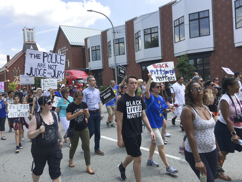 Demonstrators walk down what's normally a bustling East Liberty street, shutting down traffic Sunday as they call for justice over the death of Antwon Rose.