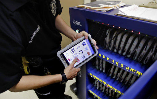 New Hampshire Department of Corrections Officer Glen Dinning puts a tablet back into a charging cabinet at the Corrections Transitional Work Center, a low-risk security section at the New Hampshire State Prison for Men, in Concord Monday, July 23, 2018.