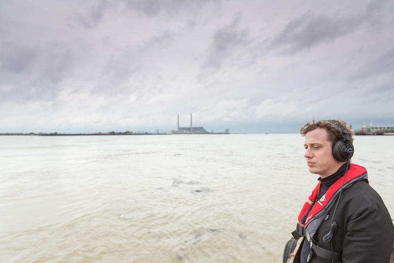 """A visitor listens to """"Waterborne"""" on the Thames Estuary."""