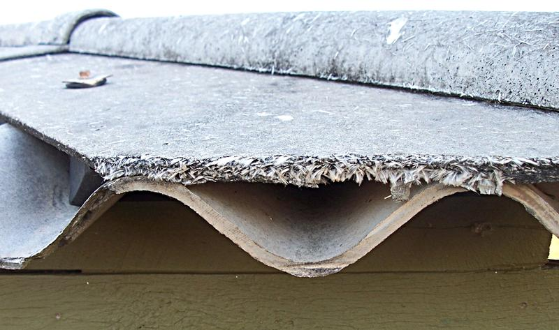 Weathered asbestos roof sheeting showing loose fibers.