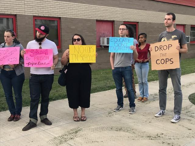 Protesters opposed rehiring local police for school security.
