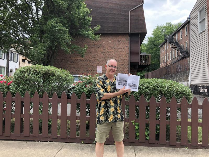 "Author and historian Donald Doherty holds his book ""Pittsburgh's Inclines"" near where the lower station of the Mount Oliver Incline would have been, prior to its dismantling in 1951."