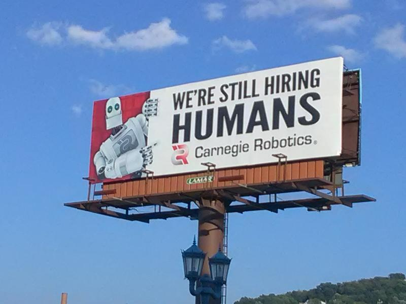 "A billboard that reads ""We're Still Hiring Humans"" stands near the east side of the 31st Street Bridge. It's advertizing open positions at Carnegie Robotics."