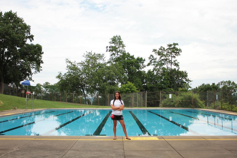 Head lifeguard Alexxis Turner stands in front of Philips Pool, one of the City of Pittsburgh's 18 outdoor swimming pools. She started as a lifeguard in 2008.