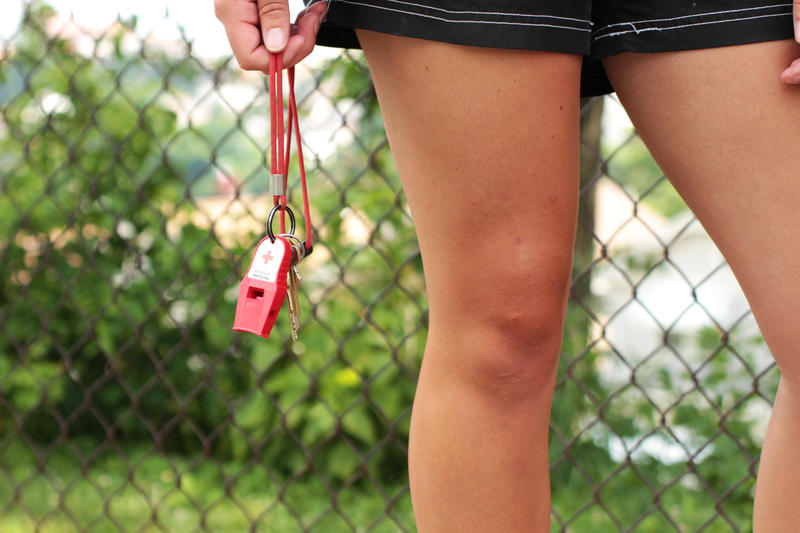 It's a standard issue American Red Cross whistle, handy for twirling while thinking or for reigning in rambunctious behavior at the pool.