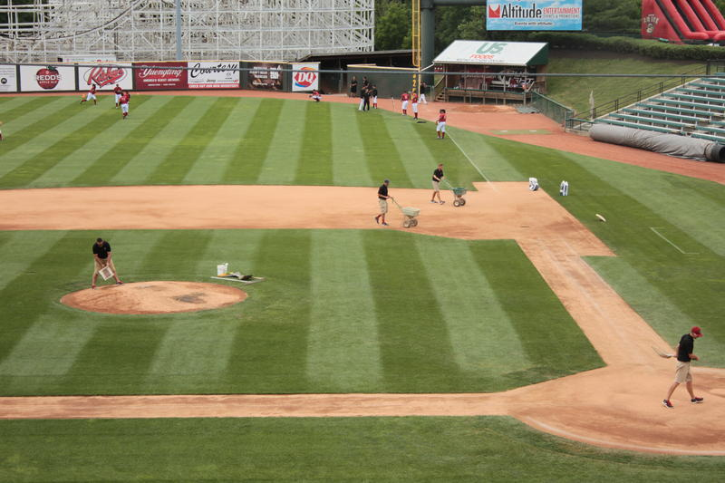 As the members of the Altoona Curve warm up in the outfield, the grounds crew also takes to the field.